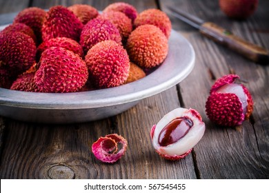 Fresh organic lychee fruit in a bowl on a rustic wooden background