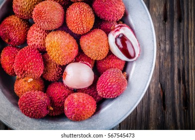 Fresh organic lychee fruit in a bowl on a rustic wooden background. Top view