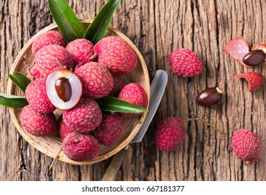 fresh organic lychee fruit on bamboo basket and old wood background, top view