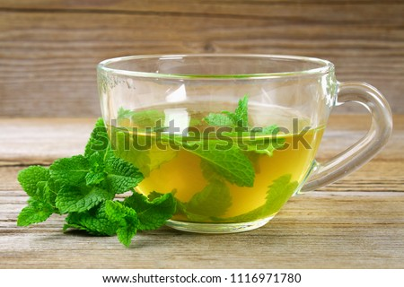 Fresh organic mint tea in glass on wooden table.