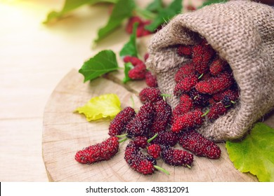 fresh organic mulberries in gunny bag with green and yellow berry leaf on wooden background.