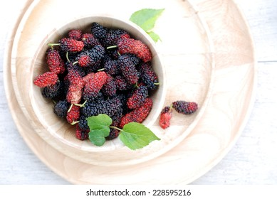 fresh organic mulberry in bowl on wooden background.