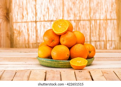 Fresh organic Orange, half of orange, orange lobule and basket with oranges on the light brown wooden table. Navel Oranges group freshly picked in a basket. Horizontal Composition. Front view. Picnic