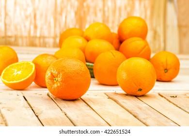 Fresh organic Orange, half of orange, orange lobule on the light brown wooden table summer background. Oranges group freshly picked in a basket. Horizontal Composition. Front view.