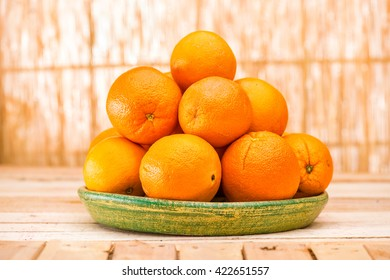 Fresh organic Orange, half of orange, orange lobule and basket with oranges on the light brown wooden table  . Navel Oranges group freshly picked in a basket. Horizontal Composition. Front view.