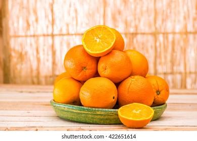Fresh organic Orange, half of orange, orange lobule on the light brown wooden table summer background. Cut set Oranges group freshly picked in a basket. Horizontal Composition. Front view.