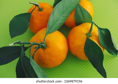 Fresh organic oranges with leaves on a green background. Close up.
