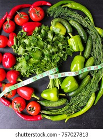 Fresh organic parsley,tomatoes,red peppers,green peppers,fennel,dill and cucumber with green centimeter on black background.top view,diet concept