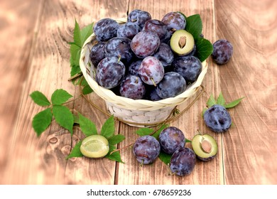 Fresh organic plum - plums in wicker basket on table