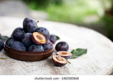 Fresh organic plums over texture wooden rustic table