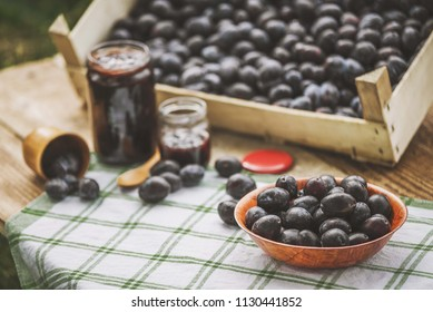 Fresh organic plums in wooden plate with jar of jam in background. Plums products. Plums on table. Plum background