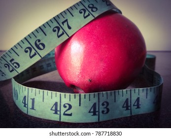fresh organic pomegranate with measuring tape