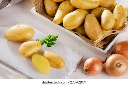Fresh organic potatoes on a white wooden cutting board.