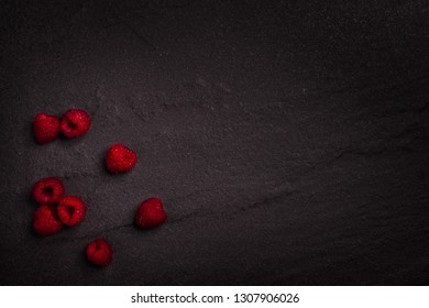 Fresh organic raspberries on a dark rock background with copy space