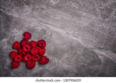 Fresh organic raspberries on a marble stone background with copy space