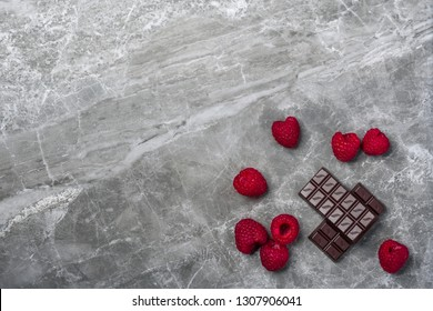 Fresh organic raspberries and two bars of organic 70% cocoa dark chocolate on a marble stone background with copy space