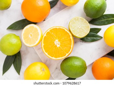 Fresh organic raw oranges with limes and lemons on marble background