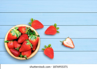 Fresh organic red berry strawberry  in wooden bowl isolated on blue wood table background. Top view. Flat lay.  Copy space.