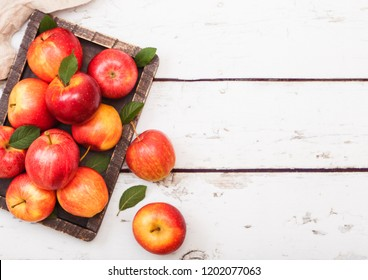 Fresh organic red healthy apples in vintage box on wooden background.