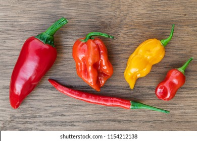 Fresh organic red, orange and yellow hot chili peppers on a wooden table