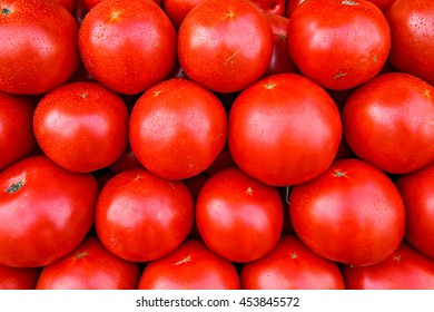 Fresh organic red tomatoes in a stack at a local farmers market.