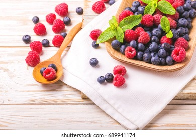 Fresh organic ripe raspberry, blackberry and blueberry with mint leaves in ceramic plate on wooden table background. Concept of healthy food. Top view
