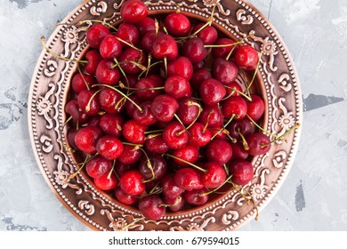 Fresh organic ripe sweet cherry on copper plate on grey marble stone background.  Summer berries. Heathy garden country vitamin  food.