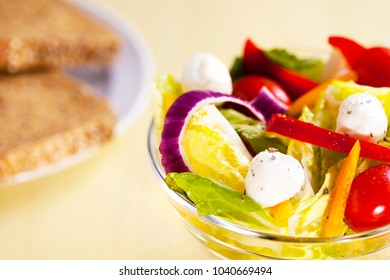 Fresh organic salad in glass bow with wholemeal bread on restaurant table