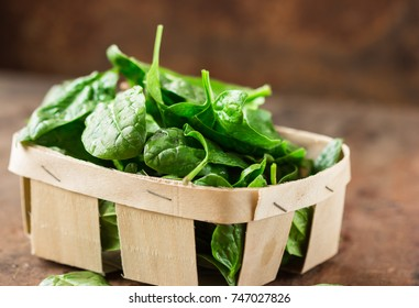 Fresh organic spinach leaves in basket on a wooden table. Diet, dieting concept. Vegan food, healthy eating.