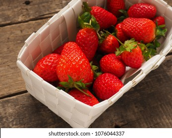 Fresh organic strawberries in a white basket on a rustic wooden table