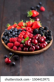 Fresh organic summer berries mix in round wooden tray on dark wooden table background. Raspberries, strawberries, blueberries, blackberries and cherries. Top view