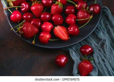 Fresh organic summer mix of strawberry and sweet cherry in round stone plate on dark textured background. Top view, still life, dark moody. Summer raw berries for healthy diet. Food lifestyle