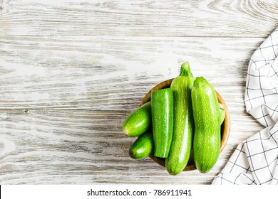 Fresh organic summer vegetables zucchini in a bowl on rustic wooden background. Top view, space for text.