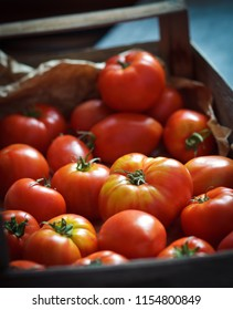 Fresh organic tomatoes in the wooden box, closeup, shallow depth of field