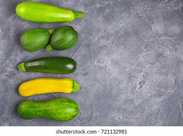 Fresh organic various zucchini  squash on grey background. Top view with copy space