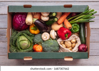Fresh organic vegetable delivery box on a wooden background - Shutterstock ID 1687307662