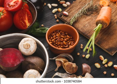 Fresh organic vegetables and beans on wood background. Wooden cutting board and knife on rustic kitchen table with natural cooking ingredients, top view, copy space