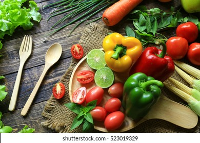 fresh organic  vegetables fork and spoon on wooden floor with copy space. concept Eat Healthy