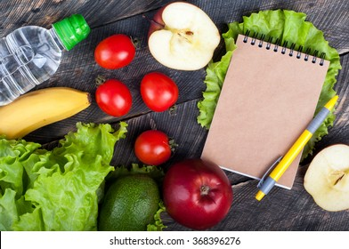 Fresh organic vegetables and fruits. Lettuce, avocado, apple, banana, water bottle, open blank notebook and pen on wooden background. Healthy food and healthy life concept. Top view