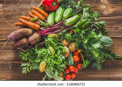 Fresh organic vegetables harvest. Local farmer market with vegetable box on wooden background, vegetarian food concept