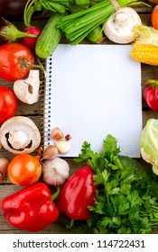 Fresh Organic Vegetables and Spices on a Wooden Background and Paper for Notes.Open Notebook and Fresh Vegetables Background.Diet.Dieting