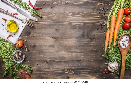 Fresh organic vegetables and spoons on rustic  wooden background, top view, border. Healthy food or vegetarian cooking concept