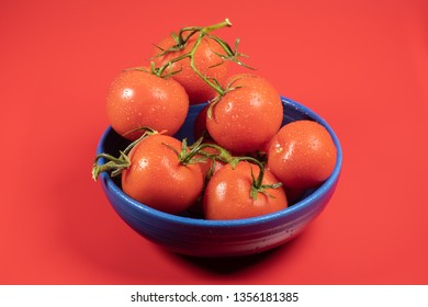 Fresh, organic whole tomatoes in a blue bowl with water drops.