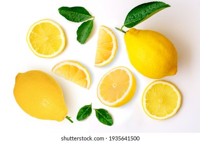 Fresh organic yellow lemon fruit with slice and green leaves isolated on white background . Top view. Flat lay.