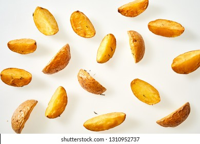 Fresh oven baked potato wedges with their skins seasoned with rosemary scattered on a white background viewed from overhead