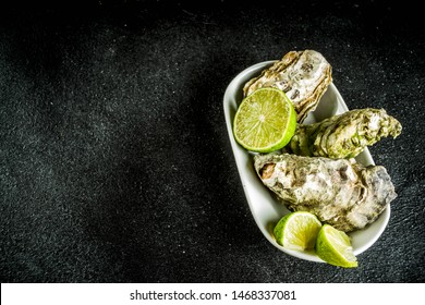 Fresh oyster clams with lemon on a black concrete background, top view copy space
