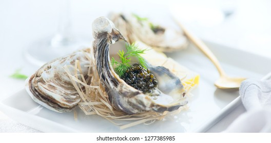 Fresh oysters with black caviar. Opened oysters with black sturgeon caviar and lemon, Gourmet food in restaurant. Delicatessen