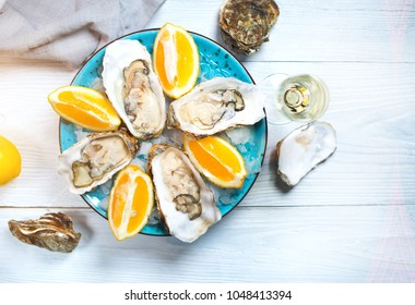Fresh Oysters close-up on blue plate, served table with oysters, lemon and ice. Table top view. Healthy sea food. Fresh raw Oyster dinner in restaurant. Gourmet food. Tabletop