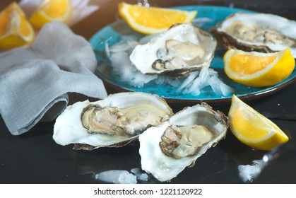Fresh Oysters close-up on blue plate, served table with oysters, lemon and ice. Healthy sea food. Oyster dinner with champagne in restaurant. Gourmet food.