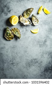 Fresh oysters, lemon wedges. Rustic stone background. Opened fresh raw oysters. Top view. Copy space. Oyster bar. Seafood. Oysters concept. Party food. Space for text. From above